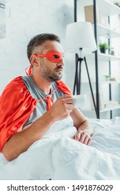 pensive man in costume of superhero drinking coffee and looking away while sitting in bed