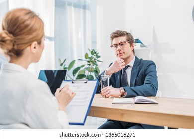 pensive man in glasses sitting near recruiter with clipboard on job interview