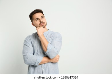 Pensive man on light background, space for text. Thinking about answer to question