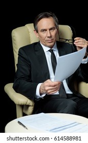 Pensive mature businessman holding eyeglasses and papers while sitting in pen isolated on black