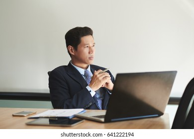 Pensive mature businessman sitting at his table and looking through window