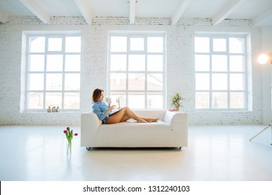 Pensive mature female freelancer drinking coffee and start working. Woman sitting on white sofa, holding cup, using laptop before three big window in white empty interior. Freelance ffreedom concept