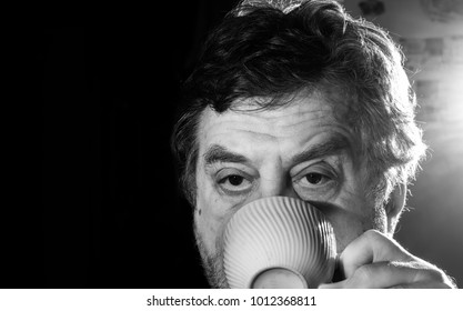 pensive mature man drinking from cap