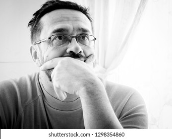 Pensive mature man with glasses close-up portrait