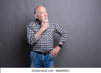 Pensive mature man looking away, copy space. Senior male dreaming about something, lost in thoughts, gray studio background