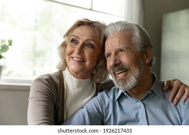 Pensive mature retired family couple looking away at window and smiling. Happy healthy married pensioners thinking of carefree retirement, planning future vacation and leisure time, hugging together