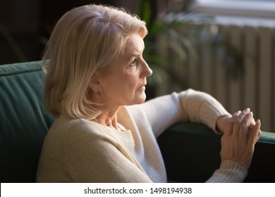 Pensive mature woman sit on couch look in distance thinking of past happy days remembering young years, thoughtful senior wife widow mourning after late deceased husband, grieving at home