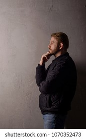 Pensive middle-aged bearded man in a black jacket and jeans stands near the wall looking away. copy space. deadpan without retouching
