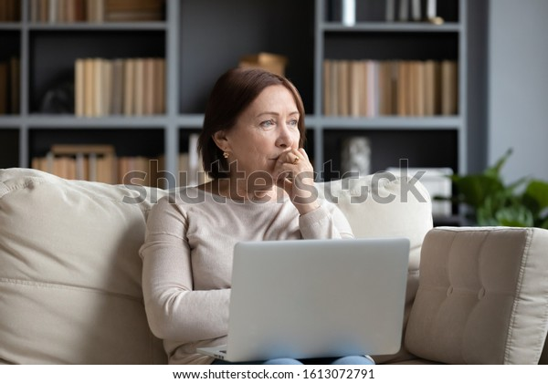 Pensive middle-aged woman sit on couch in living room using laptop look in distance thinking or pondering, thoughtful senior female distracted lost in thoughts feel lonely or sad at home