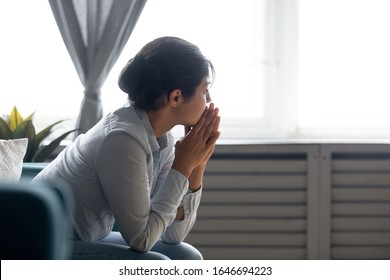 Pensive millennial Indian girl sit on couch at home look in distance thinking pondering, thoughtful young ethnic woman lost in thoughts feel stressed suffer from depression or emotional breakdown