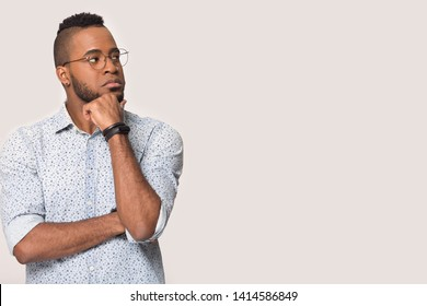 Pensive millennial mixed race man wearing shirt and glasses touch chin thinking stands aside isolated on grey or white studio background copy space for text ad, contemplating vision correction concept