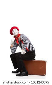 pensive mime sitting on brown suitcase isolated on white