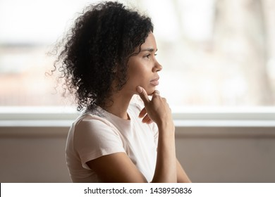 Pensive mixed race 30s woman sitting at home touch chin lost on deep thoughts thinking makes decision, side view face, challenge, problems solution, solving issues, consideration or brain work concept