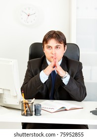 Pensive modern business man sitting at desk in office