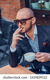 Pensive modern man is smoking a cigarette outside of coffeshop while drinking his cup of coffee.