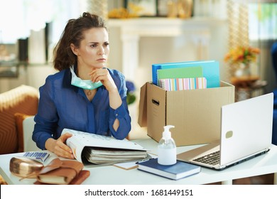 pensive modern middle age woman in blue blouse with medical mask working in temporary home office during the coronavirus epidemic in the modern house in sunny day.