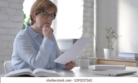 Pensive Old Woman Reading Documents at Workplace, Brainstorming Idea