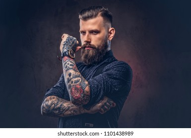 Pensive old-fashioned hipster in a blue shirt and suspenders, standing in a studio.