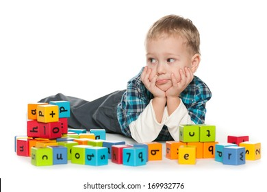 A pensive preschool boy is playing with blocks on the floor