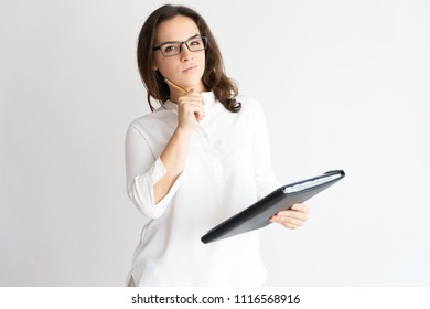 Pensive pretty woman holding file, touching face with pen and looking at camera. Business lady thinking. Paperwork concept. Isolated front view on white background.