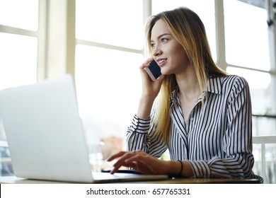 Pensive professional female recruiter making job offer to candidate through mobile conversation while working in cafe interior checking cv and documentation on laptop computer connected to wifi