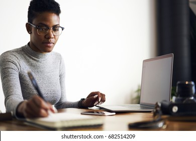 Pensive prosperous afro american graphic designer concentrated on creating blueprint drawing sketch, skilled copywriter noting ideas for advertising campaign sitting near laptop with blank screen
