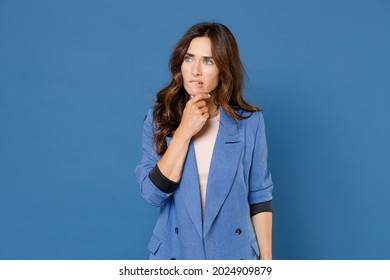 Pensive puzzled perplexed confused concerned young brunette woman 20s in basic jacket standing put hand prop up on chin looking aside isolated on bright blue colour wall background, studio portrait