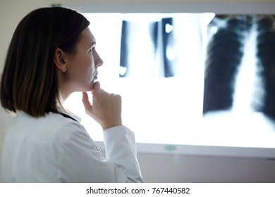 Pensive radiologist looking attentively at one of x-ray images in lab