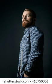 Pensive red bearded man studio portrait on dark background