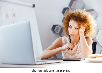 Pensive redhead curly young woman designer using laptop and grapic tablet on workplace