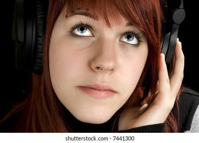 Pensive redhead girl listening to music and enjoying it (looking up, thinking). Studio shot.