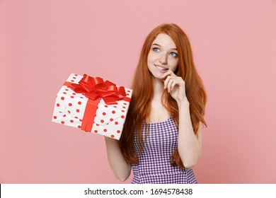 Pensive redhead girl in plaid dress isolated on pastel pink background. Valentine's Day Women's Day birthday holiday concept. Hold white red present box with gift ribbon bow, put hand prop up on chin