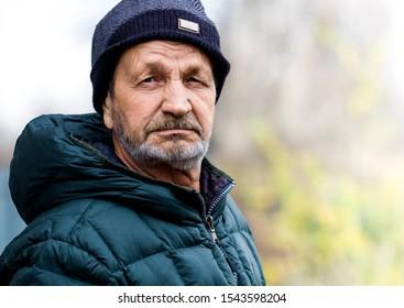 Pensive sad elderly man with a beard and mustache close-up  portrait. Russian village