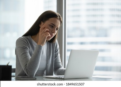 Pensive sad millennial woman office employee responsible manager spending time at office desk frowning looking at pc screen unable to find correct decision answer wrestling with difficult hard problem