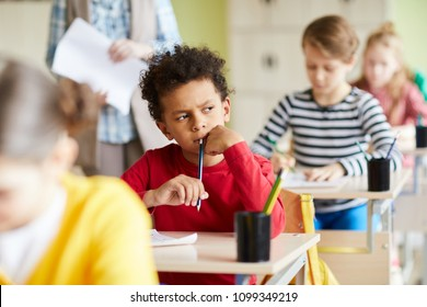 Pensive schoolboy sitting by individual desk and thinking of right answer while writing exam test