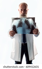 Pensive senior male doctor looking at x-ray image  isolated on white