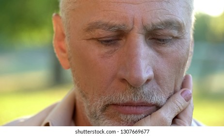 Pensive senior man thinking over life injustice, wife touching his face, support