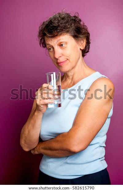 Pensive senior woman drinking water