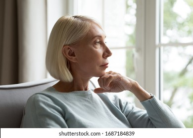 Pensive senior woman sit on couch in living room look in window distance thinking or pondering, thoughtful mature female rest on sofa at home feel alone lost in thoughts, mourning or yearning