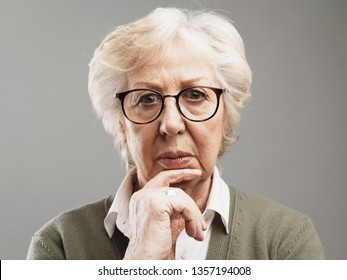 Pensive senior woman thinking with hand on chin, she is sad and concerned