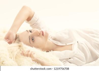 pensive sensual blond girl in white blouse lying