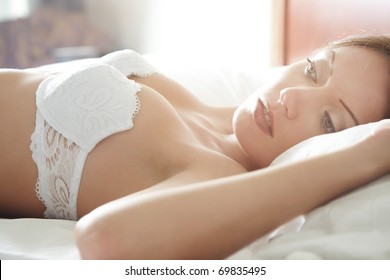 Pensive sensual woman laying in the bedroom at the early morning. Natural colors and sunlight from the window