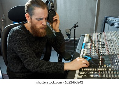Pensive serious handsome hipster young sound engineer focusing on song while mixing sound using channel audio mixer in recording studio