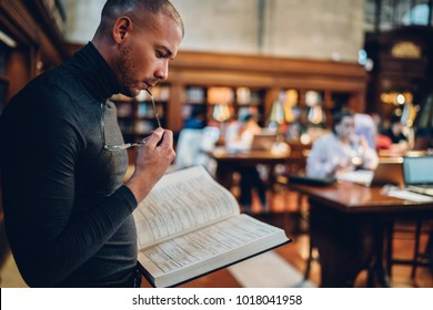 Pensive smart journalist making research in public library standing near bookshelvf, concentrated young professor reading articles in encyclopedia choosing literature for university project