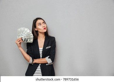 Pensive smiling asian business woman holding money and looking up over gray background