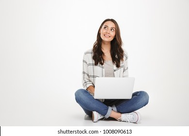 Pensive smiling brunette woman in shirt sitting on the floor with laptop computer and looking up over gray background