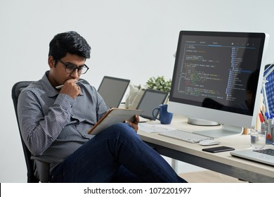 Pensive software developer analyzing data in tablet computer
