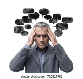 Pensive stressed man having negative thoughts and feeling confused, he is surrounded by dark speech bubbles