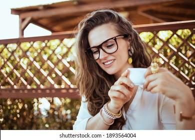 pensive stylish 40 years old housewife in white shirt with cup of coffee and eyeglasses in the terrace.