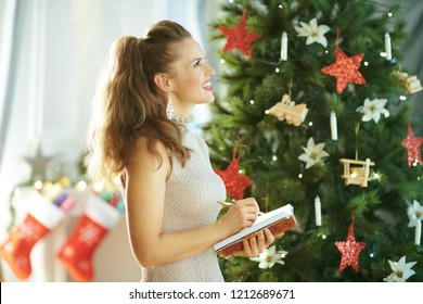 pensive stylish housewife near Christmas tree writing in notebook